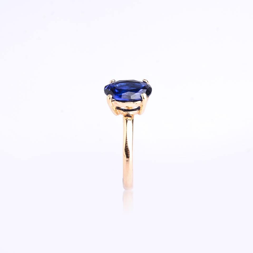 Semi joia anel dourado com zircônia oval azul.