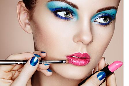 Fotografia de mulher sendo maquiada.