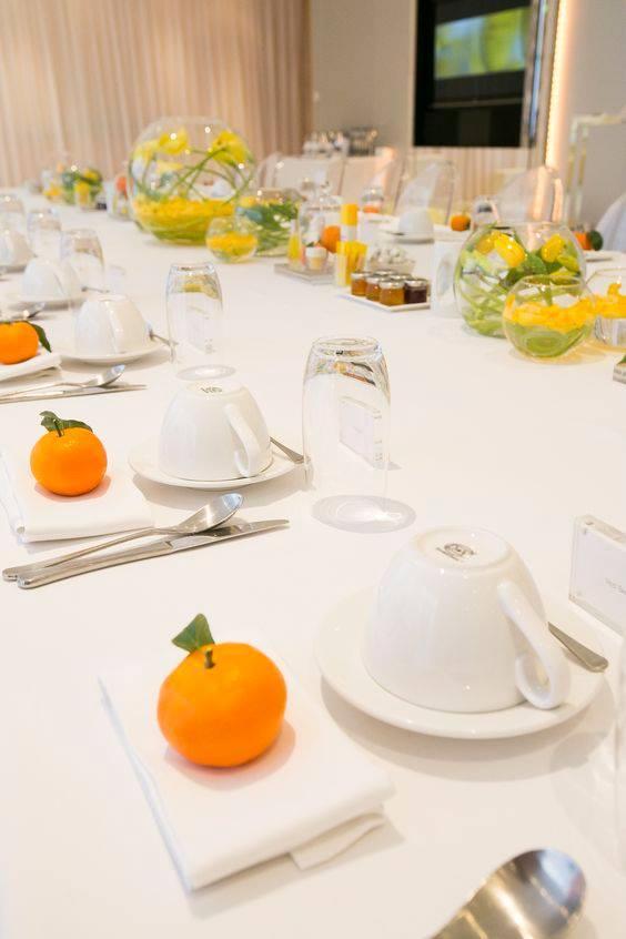 decoração de mesa com toalha de mesa oxford branca e arranjos de laranja