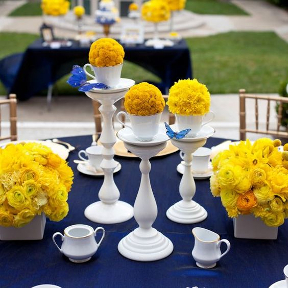 mesa posta com toalha de mesa azul royal com arranjos amarelos