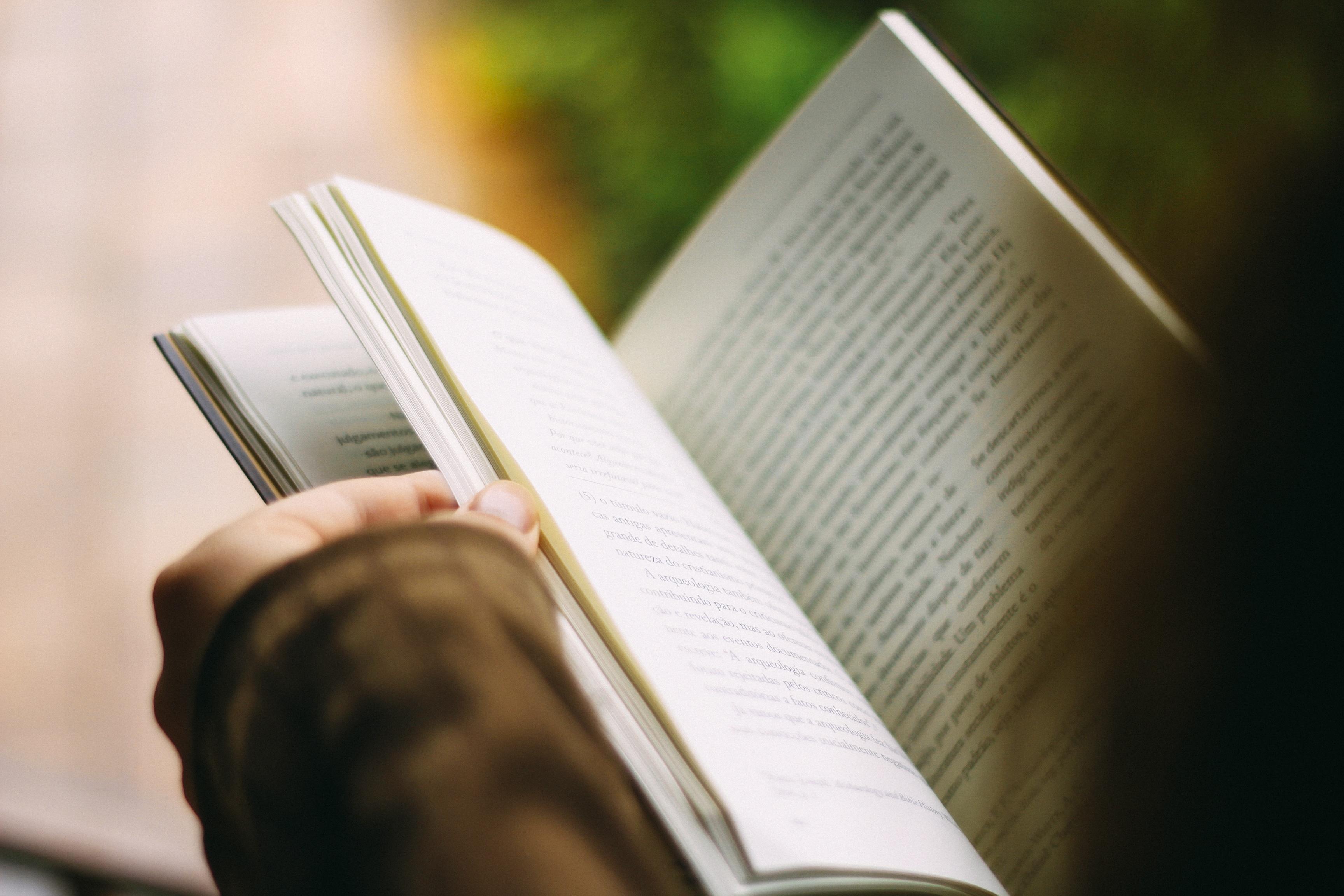 Close de pessoa segurando um livro. Imagem ilustrativa texto preço do livro.