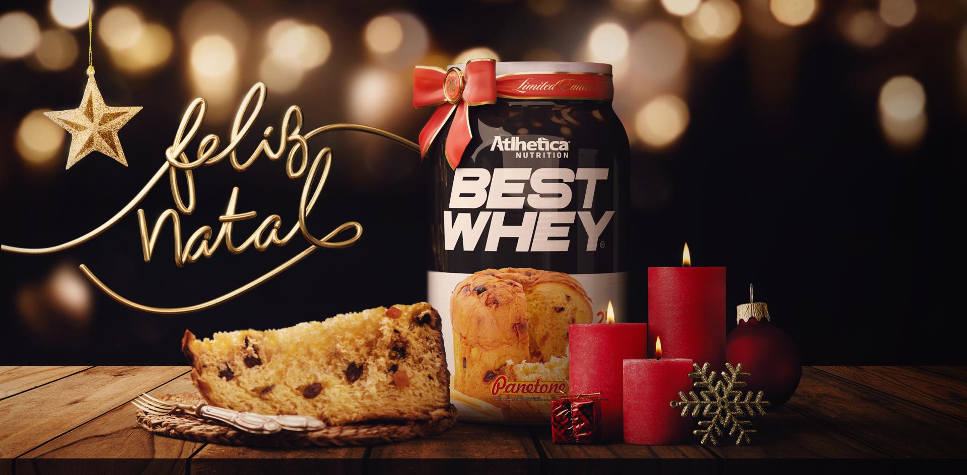 Best Whey 900g Panetone sobre uma mesa com itens de natal e um fio dourado escrito Feliz Natal ao fundo