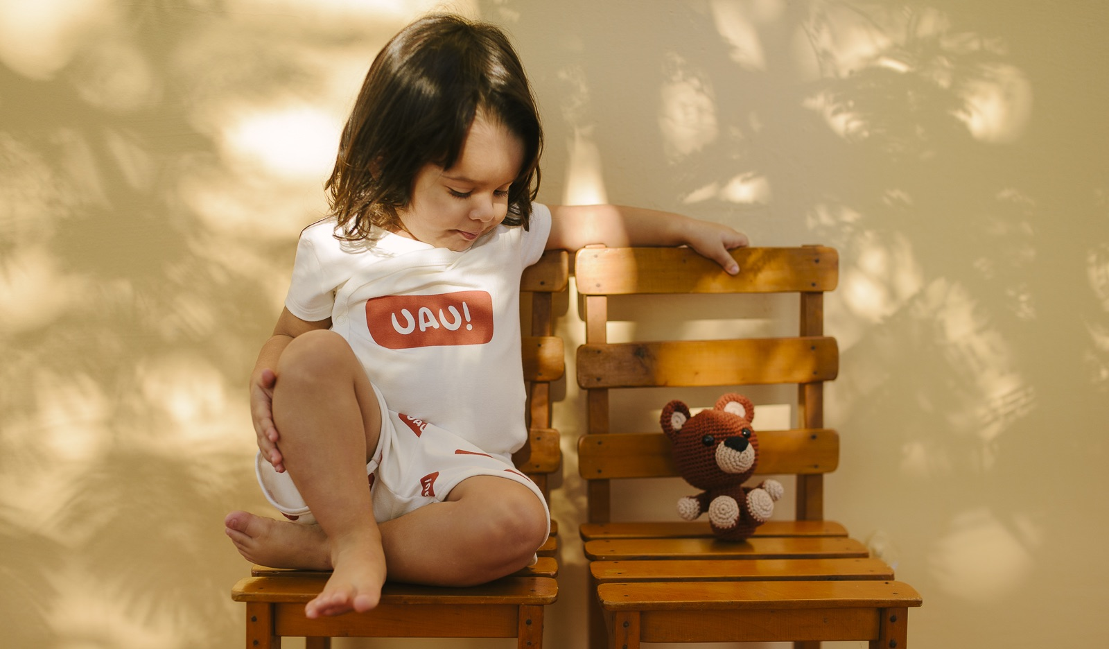 criança vestindo camiseta uau e urso de pelúcia