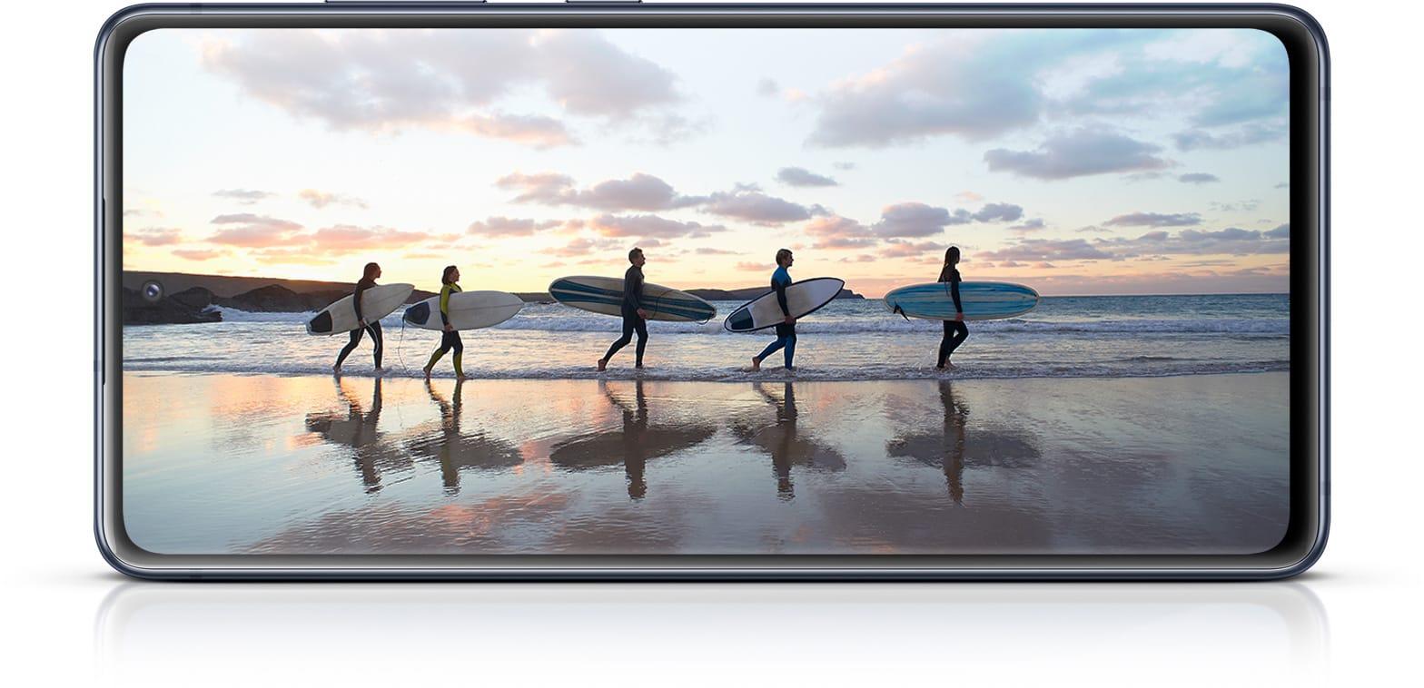 Galaxy S20 FE com uma foto de surfistas na tela, mostrando a imersão do Infinity-O Display.