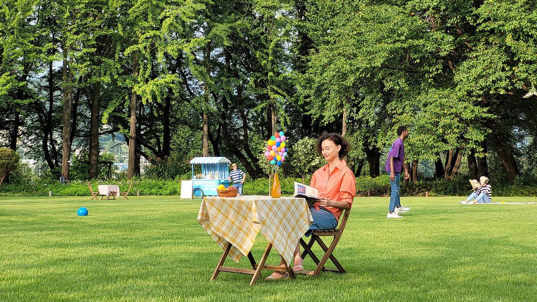 Foto ampliada 3x, chegando mais perto de uma mulher sentada sozinha. Há uma mesa no fundo da foto com zoom 1x.