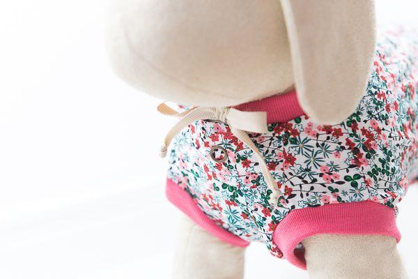 Camiseta gola careca de malha super leve em floral fundo branco com flores rosas e detalhe na gola combinando