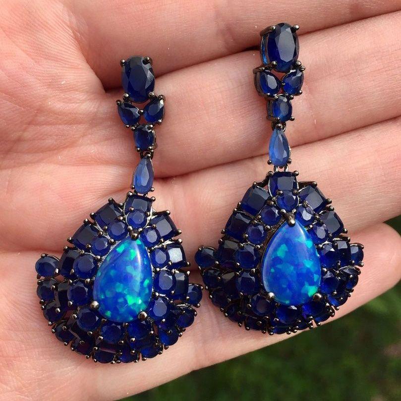 Brinco longo banhado a ródio negro cravejado com pedra cristal azul e pedra cristal fundida com pedra Opala