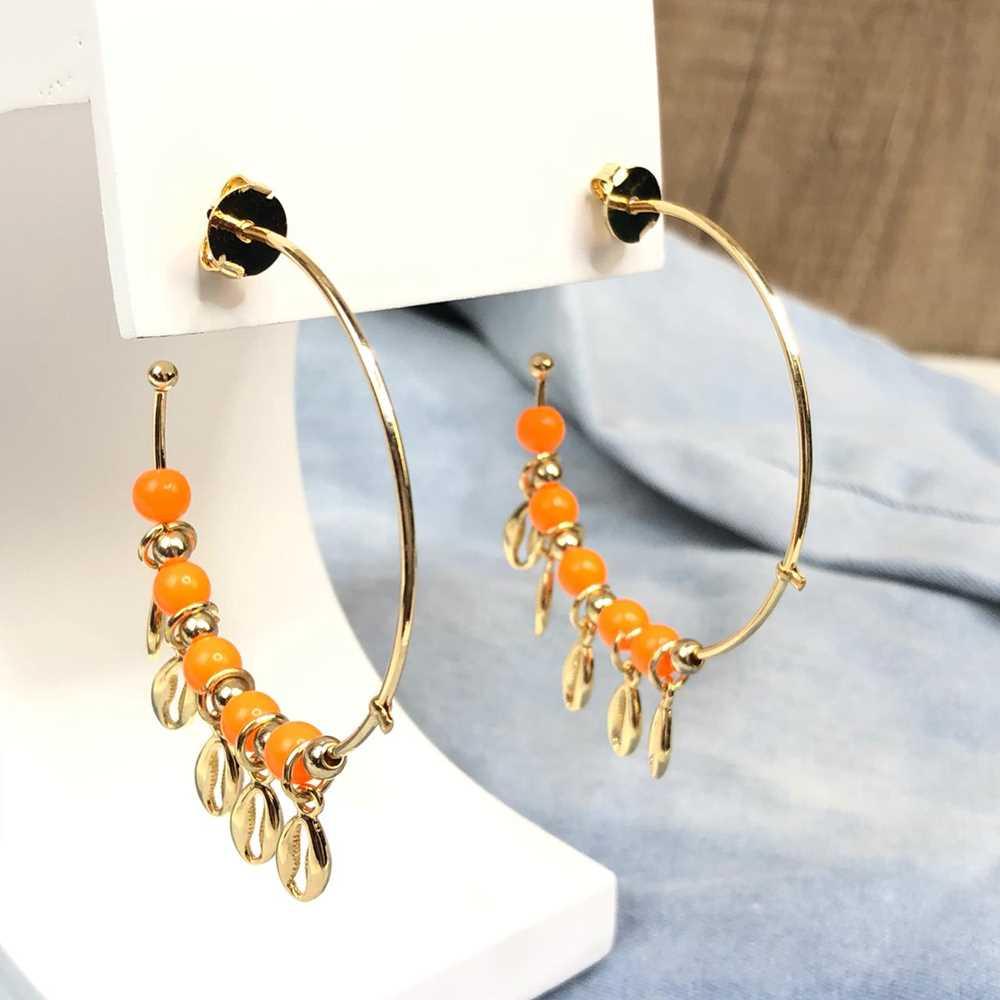 Brinco de argola dourada com miçanguinhas laranja e pingentes de búzios