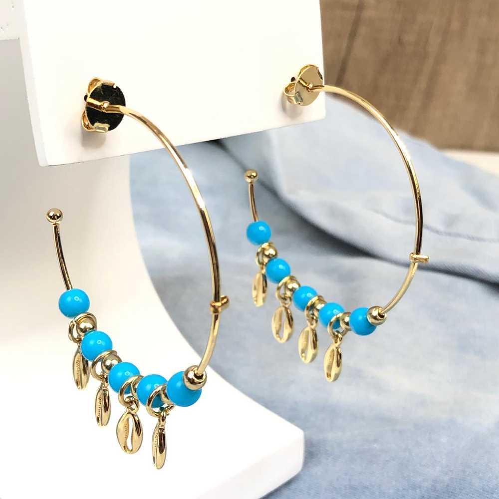 Brinco de argola dourada com miçanguinhas azul e pingentes de búzios