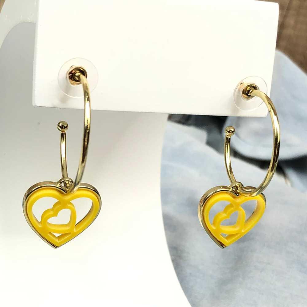 Brinco de argola dourada com pêndulo de coração em acrilico vazado amarelo