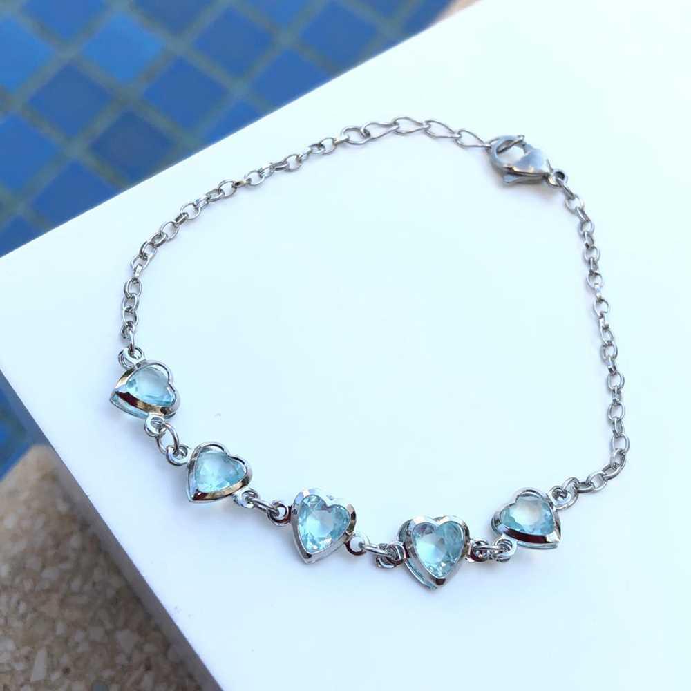 Pulseira de aço feminina com pedrarias de coração azul bebê