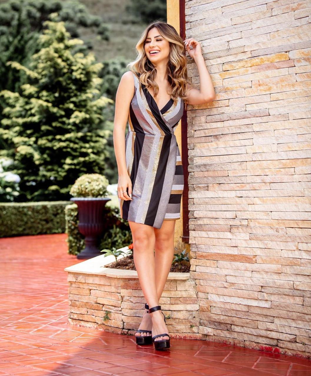 Vestido curto paetês Gold Moments em poliéster e elastano, decote transpassado, alças largas não ajustáveis e fechamento por zíper na parte lateral com forro.