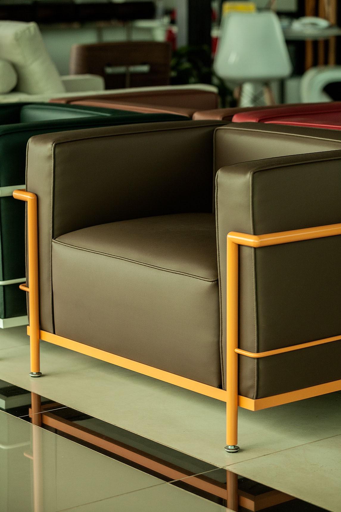 Poltrona LC3 - estrutura em aço carbono pintado em laca laranja e revestimento em Couro Ecológico Marrom Capuccino.