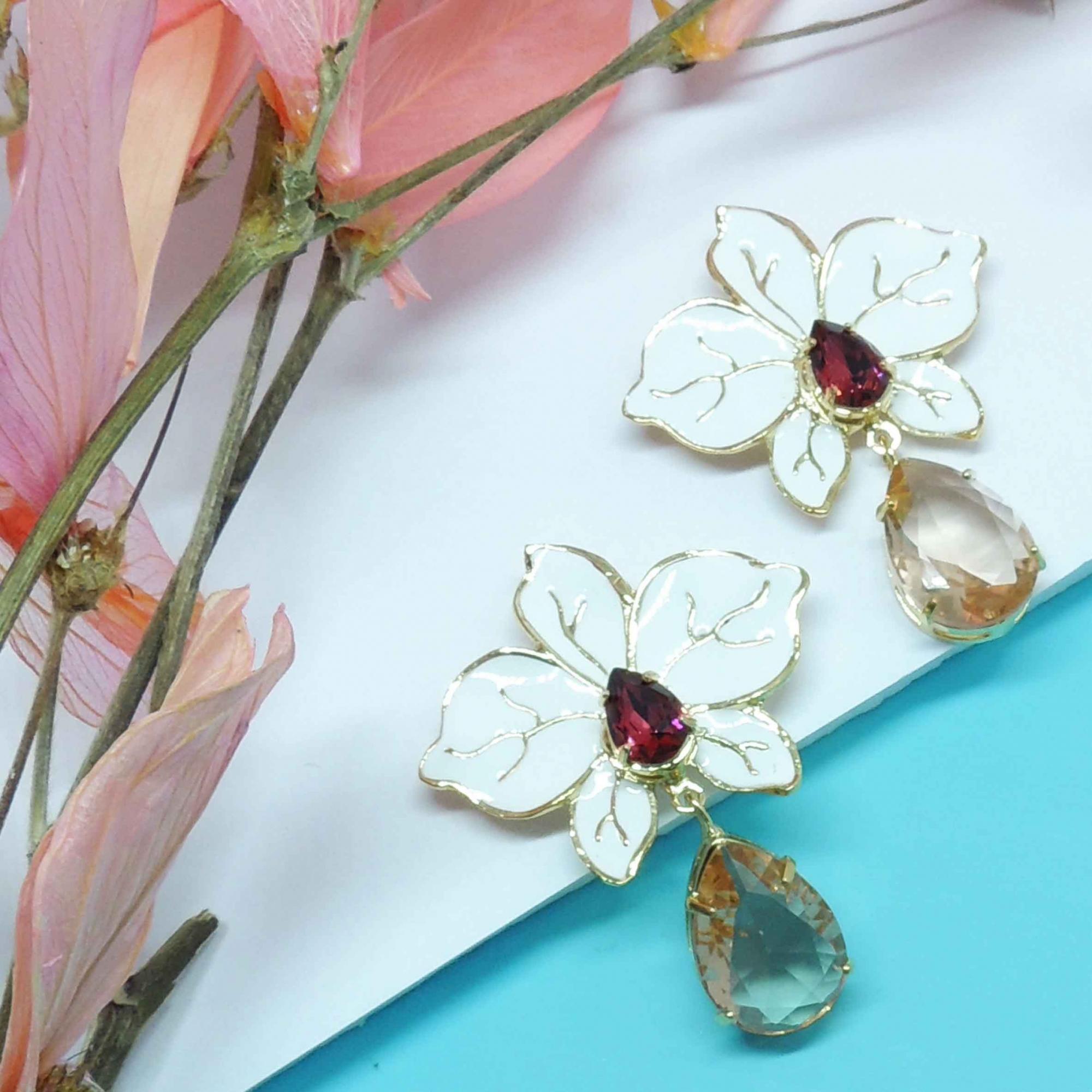 Brinco feminino em formato de orquídea branca com pedras rosa, família botânica