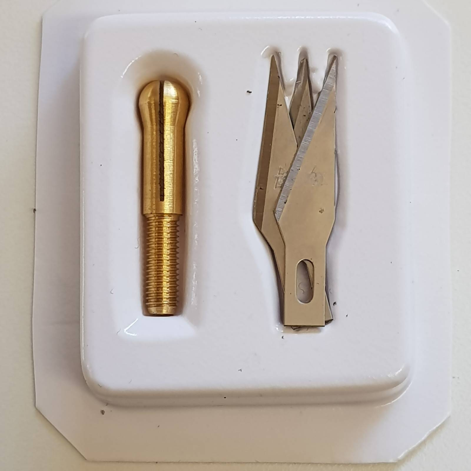 Blister with three blades and tweezers for use on the interchangeable handle