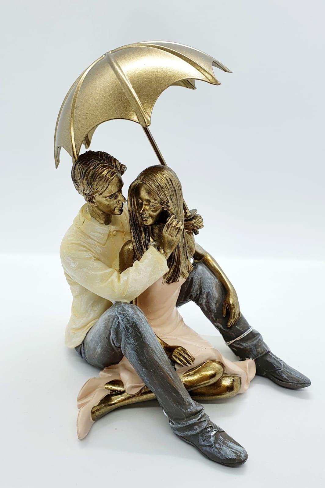 Escultura casal sentados guarda chuva